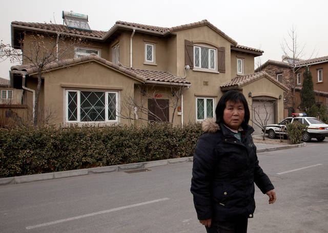 In this Saturday, March 9, 2013 photo, Zhao Meifu, a farmer from Gansu province, walks past a house in Beijing, where she claims to have been held with other petitioners before being sent to a labor camp last year in China's arid northwest. Zhao had been seeking redress for decades over a land grab by village officials. Tired of her complaints, police saw the labor camp as a quick way to get rid of her. Long hated and often abused, a notorious penal system that allows Chinese police to lock up people for up to four years without a trial or a judge's review has come under scrutiny. Cases like Zhao's last year have galvanized critics, many of them within the government, and China's newly installed leadership is seizing on the expectations for reform. (AP Photo/Andy Wong)