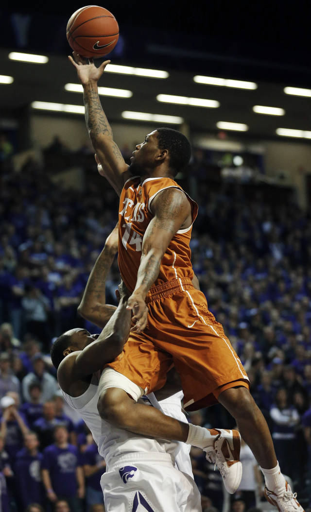 Texas guard Julien Lewis (14) is fouled by Kansas State guard Martavious Irving (3) during the first half of an NCAA college basketball game in Manhattan, Kan., Wednesday, Jan. 30, 2013. (AP Photo/Orlin Wagner)