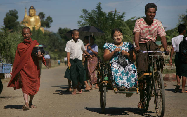 In this photo taken on Nov. 7, 2012, an ethnic Rakhine Buddhist woman rides in a trishaw as a Buddhist monk walks expecting alms in Pauk Taw, Rakhine state, western Myanmar. Stranded beside their decrepit flotilla of wooden boats, on a muddy beach far from home, the Muslim refugees tell story after terrifying story of their exodus from a once-peaceful town on Myanmar's western coast. The Oct. 24 exodus was part of a wave of violence that has shaken western Myanmar twice in the last six months.  (AP Photo/Khin Maung Win)