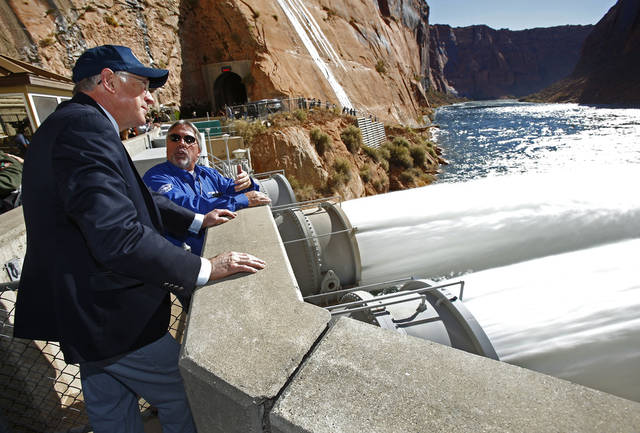 Interior Secretary Ken Salazar, left, watches the high-flow release of water into the Colorado River from bypass tubes at Glen Canyon Dam in Page, Ariz., Monday Nov. 19. 2012. Federal water managers began started a 5-day high-flow experimental release to help restore the Grand Canyon's ecosystem. (AP Photo/The Arizona Republic, Rob Schumacher) MARICOPA COUNTY OUT; MAGS OUT; NO SALES