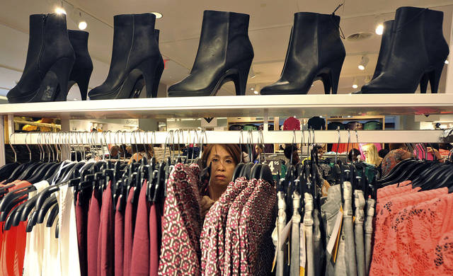FILE - In this Thursday, Sept. 6, 2012, photo, a woman shops at The Avenues Mall in Jacksonville, Fla. Americans took out more student and auto loans in September to boost consumer borrowing to a record level. But they cut back on credit card borrowing, a sign many remain cautious about taking on high-interest debt. (AP Photo/Florida Times-Union, Bruce Lipsky, File)
