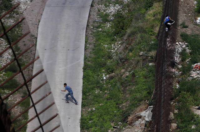 FILE - In this July 28, 2010 photo, two men illegally cross the border fence separating Nogales, Ariz., and Nogales, Sonora, Mexico, Arizona launched a website Wednesday, July 20, 2011, to accept donations to pay for fencing along the Mexico border, and a supporter says the $3.8 million people donated to defend the state's 2010 immigration enforcement law could be just a taste of what to expect. (AP Photo/Jae C. Hong, File)