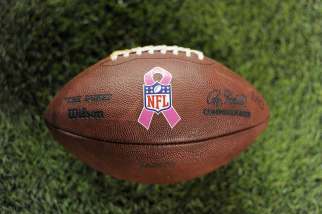 FILE - In this Oct. 28, 2012 file photo, a pink ribbon adorns the official game ball to support Breast Cancer Awareness during an NFL football game between the Denver Broncos and the New Orleans Saints Sunday Oct. 28, 2012, in Denver.  From pink baseball bats to pink penalty flags, professional sports organizations have recognized women by supporting breast cancer awarness.  (AP Photo/Jack Dempsey, File)