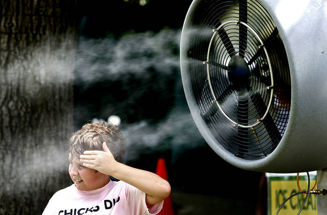 Aaron Emery, 11, of Tulsa, wipes his forehead as he tries to get cooled off in front of a mist fan during the first round of practice for the 2007 PGA Championship at Southern Hills Country Club on Monday, Aug. 6, 2007, in Tulsa, Okla.   staff photo by CHRIS LANDSBERGER  ORG XMIT: KOD