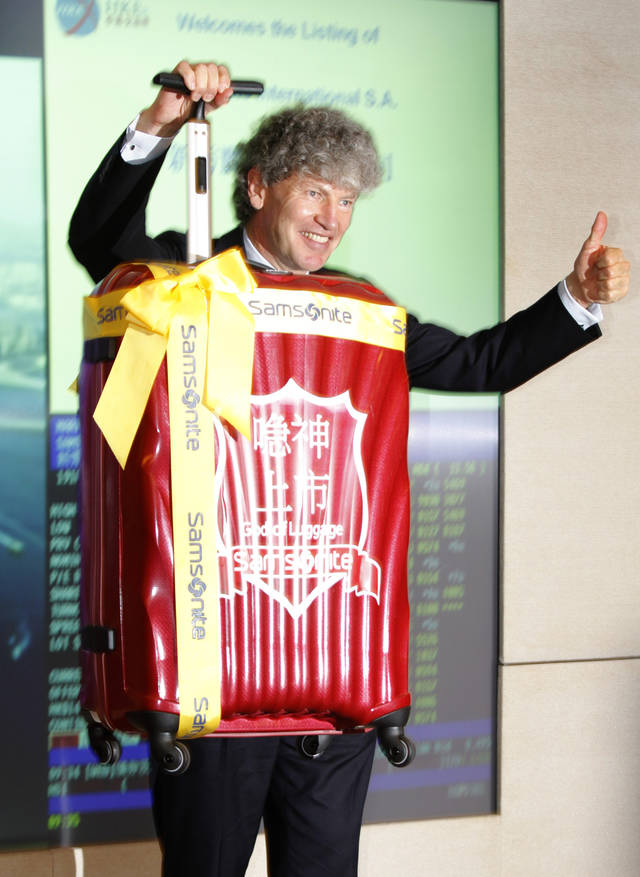 Chairman of Samsonite International S.A. Tim Parker poses with a suitcase, a souvenir for the Hong Kong Stock Exchange, during the trading debut of Samsonite International in Hong Kong Thursday, June 16, 2011. Shares of the luggage maker plunged on their first day of trading, amid waning investor interest in IPOs as global stock markets slide. (AP Photo/Vincent Yu)