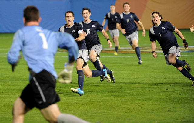 Georgetown players run to celebrate with goalkeeper Tomas Gomez (1) after they defeated Maryland on penalty kicks in an NCAA College Cup men's soccer championship semifinal match at Regions Park, Friday, Dec. 7, 2012, in Hoover, Ala. (AP Photo/ AL.com, Mark Almond) MAGS OUT
