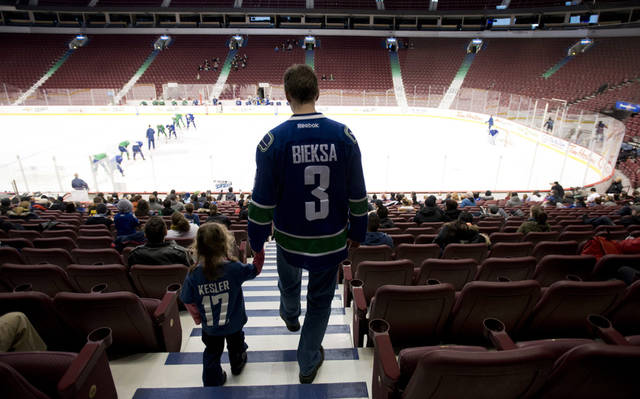 Brad Cavanagh and his three-year-old daughter Elizabeth arrive to watch the Vancouver Canucks during NHL hockey training camp at Rogers Arena in Vancouver, British Columbia, Tuesday, Jan., 15, 2013. (AP Photo/The Canadian Press, Jonathan Hayward)