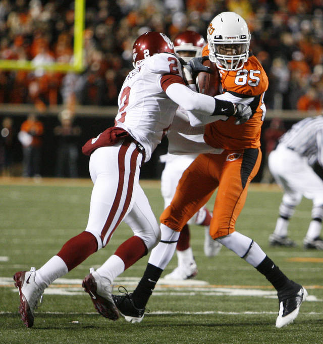 Oklahoma State's Damian Davis is hit by Brian Jackson of Oklahoma during the first half of the college football game between the University of Oklahoma Sooners (OU) and Oklahoma State University Cowboys (OSU) at Boone Pickens Stadium on Saturday, Nov. 29, 2008, in Stillwater, Okla. STAFF PHOTO BY NATE BILLINGS