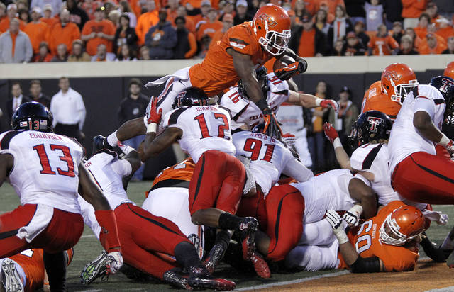 Oklahoma State's Joseph Randle (1) leaps over the line of scrimmage for a touchdown during the college football game between the Oklahoma State University Cowboys (OSU) and Texas Tech University Red Raiders (TTU) at Boone Pickens Stadium on Saturday, Nov. 17, 2012, in Stillwater, Okla.   Photo by Chris Landsberger, The Oklahoman