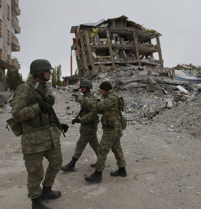 "Turkish soldiers stand next to the rubble as they search for Tahir Ormanoglu, a teacher, 27, believed to be trapped beneath, as hopes of finding more survivors were dimming in Ercis, Van Turkey, Saturday, Oct 29, 2011. At least three people were brought alive from the block of apartments earlier, including a two-week-old baby. ""My kid, my kid, my kid,"" the mother cried, clutching and kissing a photo of her son as she watched the rescue operation from inside of a fire engine. (AP Photo/Burhan Ozbilici)"
