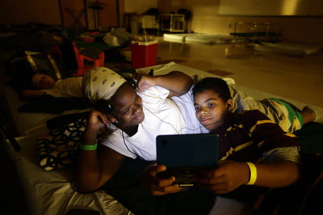 Crystal Medley, left, and her son Christian Jackson 11, play a video game at a shelter at Washington High School, in the aftermath of superstorm Sandy, Tuesday, Oct. 30, 2012, in Princess Anne, Md. (AP Photo/Alex Brandon) ORG XMIT: MDAB113