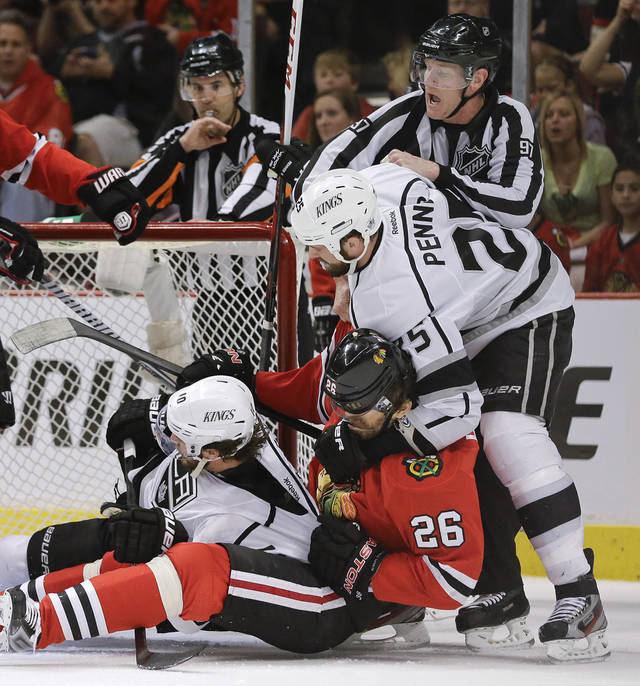 Los Angeles Kings left wing Dustin Penner (25) grabs Chicago Blackhawks center Michal Handzus (26), who pulls down Los Angeles Kings center Mike Richards (10) during a fight in the first period of Game 1 of the NHL hockey Stanley Cup Western Conference finals, Saturday, June 1, 2013, in Chicago. (AP Photo/Nam Y. Huh)