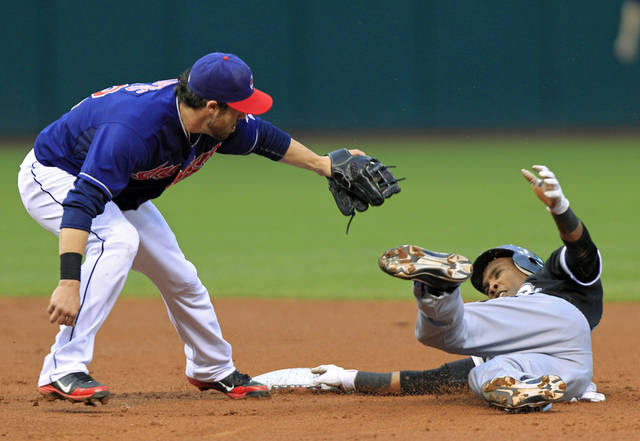 Cleveland Indians second baseman Jason Kipnis, left, holds up his glove after tagging out Chicago White Sox's Alexei Ramirez trying to steal second in the second inning of the second game of a baseball doubleheader Monday, May 7, 2012, in Cleveland. (AP Photo/Mark Duncan)