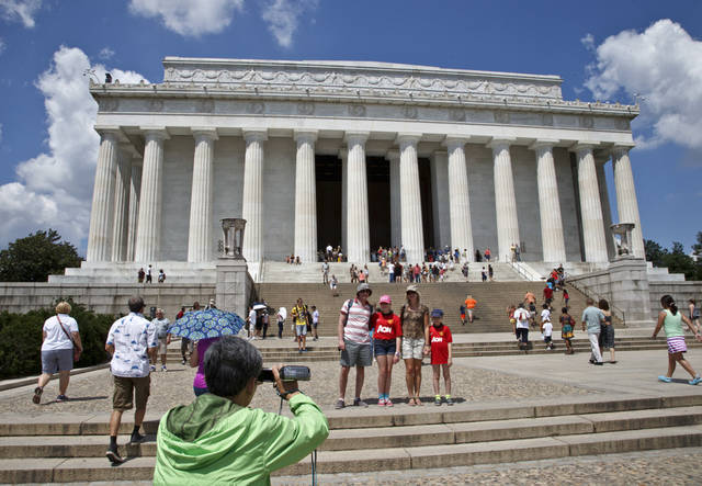 Tourists flock to the Lincoln Memorial in Washington, Friday, July 26, 2013, after someone splattered green paint on the statue of the 16th president and the floor area. Police say the apparent vandalism was discovered early Friday morning with no words, letters or symbols visible in the paint. (AP Photo/J. Scott Applewhite)
