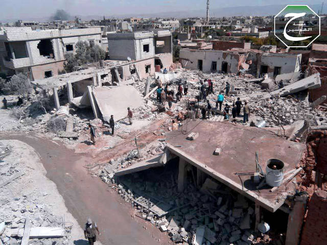 FILE - This Tuesday, May 21, 2013 file citizen journalism image provided by Qusair Lens, which has been authenticated based on its contents and other AP reporting, shows Syrian citizens gathering over houses that were destroyes from a Syrian forces air strike in the town of Qusair, near the Lebanon border, Homs province, Syria. Cut off for three weeks by a regime siege, doctors in the Syrian town of Qusair keep hundreds of wounded in storerooms and underground shop cellars, short on antibiotics and anesthesia, using unsterilized cloth for bandages and blowing air with pumps because there's no oxygen canisters, amid relentless shelling and sniper fire. More than a dozen have died from untreated wounds and at least 300 others need immediate evacuation, one doctor says. (AP Photo/Qusair Lens, File)