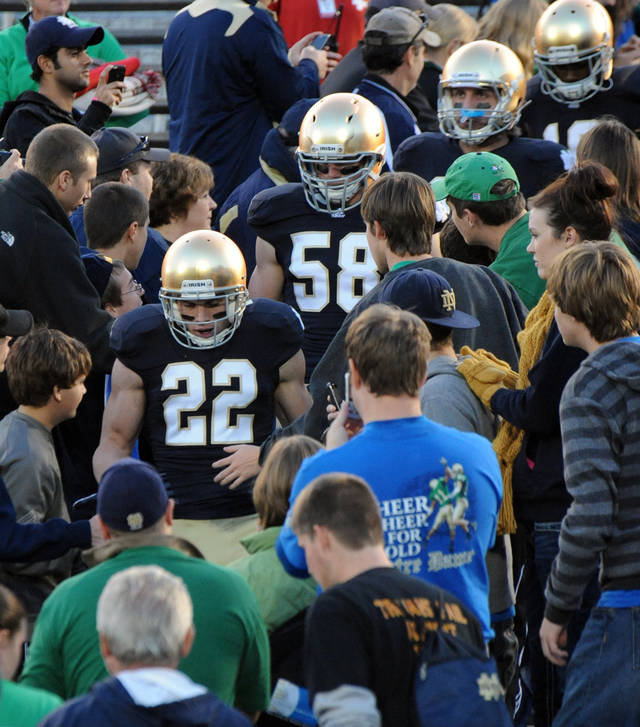 Notre Dame safety Harrison Smith (22) leads players through the student section before an NCAA college football game between Notre Dame and Southern California in South Bend. Ind., Saturday, Oct. 22, 2011. (AP Photo/Joe Raymond) ORG XMIT: INJR101