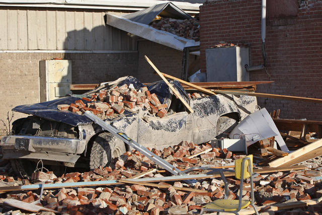 A truck is covered in rubble April 15, 2011, outside a school in Tushka after an overnight tornado. AP file photo