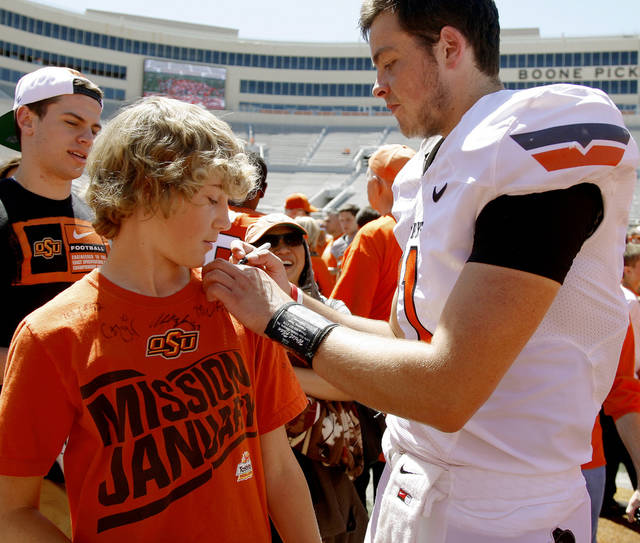 OSU's Wes Lunt signs the shirt of twelve-year-old Luke Fritzler of Enid after Oklahoma State's spring football game at Boone Pickens Stadium in Stillwater, Okla., Saturday, April 21, 2012. Photo by Bryan Terry, The Oklahoman