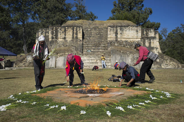 Mayan priests place flowers for a ceremony at Iximche archeological site in preparation for the Oxlajuj B'aktun in Tecpan, Guatemala, Thursday, Dec. 20, 2012.  The Oxlajuj B'aktun is on Dec. 21, marking a new period in the Mayan calendar, an event only comparable in recent times with the new millennium in 2000. While the Mayan calendar cycle has prompted a wave of doomsday speculation across the globe, few in the Mayan heartland believe the world will end on Friday.  (AP Photo/Moises Castillo)