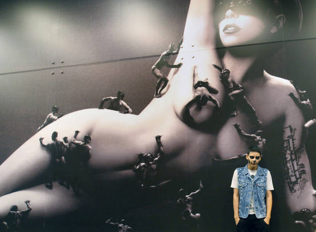 A fan of U.S. singer Lady Gaga poses in front of banner with an image of her during a welcoming demonstration ahead her visit in Lima, Peru, Monday, Nov. 12, 2012. Lady Gaga will perform on Nov. 23 in Lima. (AP Photo/Karel Navarro)