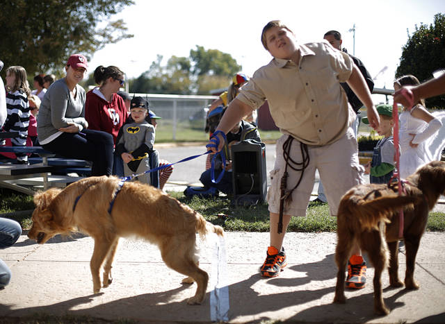 Tyler Thomason, 11 of Yukon, tries to control his dog, Harley, during a dog and child costume show at the Yukon Community Center in Yukon, Okla., Saturday, Oct. 27, 2012.  Thomason was dressed as a lion tamer, and Harley, a lion.  Photo by Garett Fisbeck, The Oklahoman