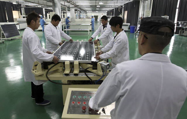 In this photo taken Wednesday March 21, 2012, Chinese workers assemble solar panels at a manufacturer of photovoltaic products in Huaibei in central China's Anhui province. China's government on Friday, May 18, 2012, rejected a U.S. antidumping ruling against its makers of solar power equipment and Chinese manufacturers warned proposed punitive tariffs might hurt efforts to promote clean energy. (AP Photo) CHINA OUT