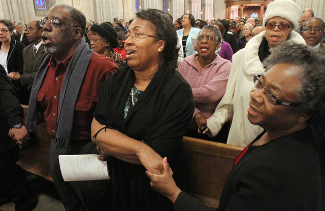 From left, Robert Jones, Alma Mickens Jones and Miriam McIntosh sing &quot;We Shall Overcome&quot; on Sunday, Jan. 20, 2013 during The Rev. Martin Luther King, Jr. Commemoration Service at Duke Chapel in Durham, N.C. (AP Photo/The Herald-Sun, Christine T. Nguyen)