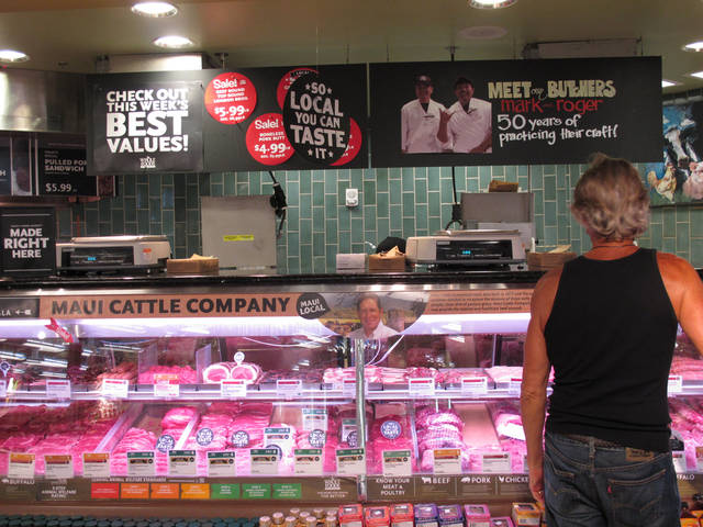 A customer looks at the meat display at the Whole Foods Market Kahala store in Honolulu on Sept. 28, 2012. National trends in locally grown foods and grass-fed beef have caught on in Hawaii, but crushing drought has made it difficult for ranchers to keep enough cattle in Hawaii to capitalize on the demand. (AP Photo/Audrey McAvoy)