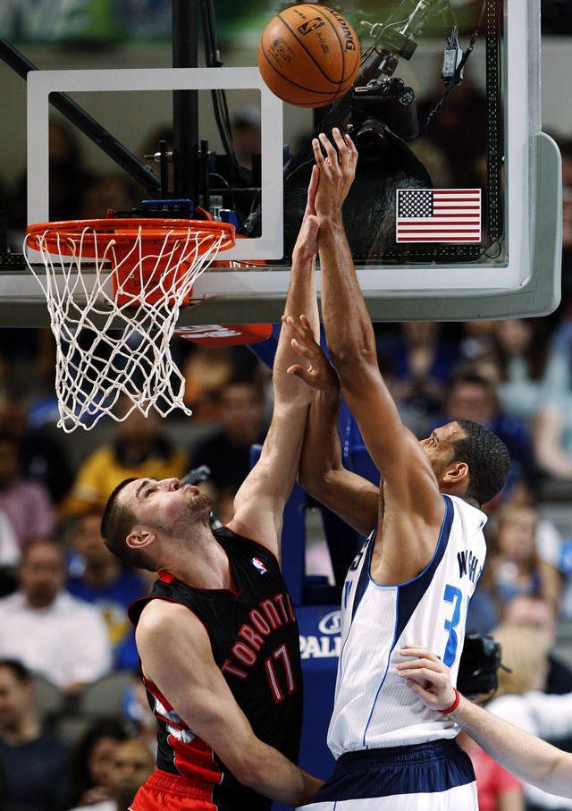 Toronto Raptors' Jonas Valanciunas (17), of Lithuania, breaks up a dunk attempt by Dallas Mavericks' Brandan Wright (34) in the first half of an NBA basketball game, Wednesday, Nov. 7, 2012, in Dallas. (AP Photo/Tony Gutierrez)