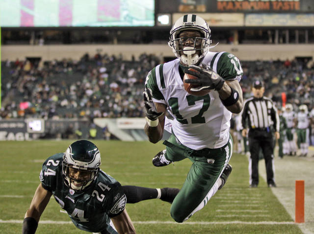 FILE - In this Dec. 18, 2011, file photo, New York Jets wide receiver Plaxico Burress (17) catches a pass for a touchdown in front of Philadelphia Eagles cornerback Nnamdi Asomugha (24) during the second half of an NFL football game in Philadelphia. The Pittsburgh Steelers signed Burress on Tuesday, Nov. 20, 2012, to provide depth at a position decimated by injuries. (AP Photo/Matt Slocum, File)