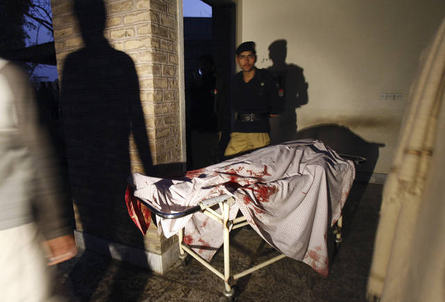 A Pakistani policeman stands next to the body of an aid worker, who was killed by gunmen, at a hospital in Swabi, Pakistan, Tuesday, Jan. 1, 2013. Gunmen in northwest Pakistan killed at least five female teachers and two aid workers on Tuesday in an ambush on a van carrying workers home from their jobs at a community center, officials said. (AP Photo/Mohammad Sajjad)