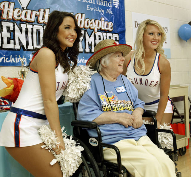 Thunder girls Bailee, left, and Sarah pose with nursing home resident Nancy Wenger at the Senior Olympics.