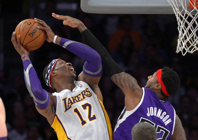 Los Angeles Lakers center Dwight Howard, left, puts up a shot as Sacramento Kings forward James Johnson defends during the first half of their NBA basketball game, Sunday, Nov. 11, 2012, in Los Angeles. (AP Photo/Mark J. Terrill)
