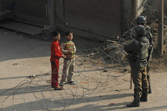 Kashmiri children ask Indian paramilitary soldiers permission to cross barbed wire set up as road block by soldiers on the fourth consecutive day of curfew imposed after the execution of a Kashmiri man convicted in a deadly 2001 attack on India's Parliament in Srinagar, India, Tuesday, Feb. 12, 2013. Mohammed Afzal Guru was hanged in New Delhi early Saturday. Ahead of the execution, authorities had anticipated anti-India protests and ordered people in most of the Indian-held part of the disputed Kashmir region to remain indoors indefinitely. (AP Photo/ Mukhtar Khan)