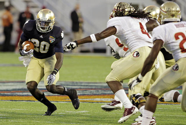 Notre Dame running back Cierre Wood (20) runs past Florida State defenders Terrance Parks (4) and Xavier Rhodes, right, during the first half of the Champs Sports Bowl NCAA college football game, Thursday, Dec. 29, 2011, in Orlando, Fla. (AP Photo/John Raoux)