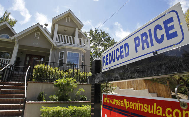 Exterior view of home with a reduced price sign in Palo Alto, Calif. AP Photo