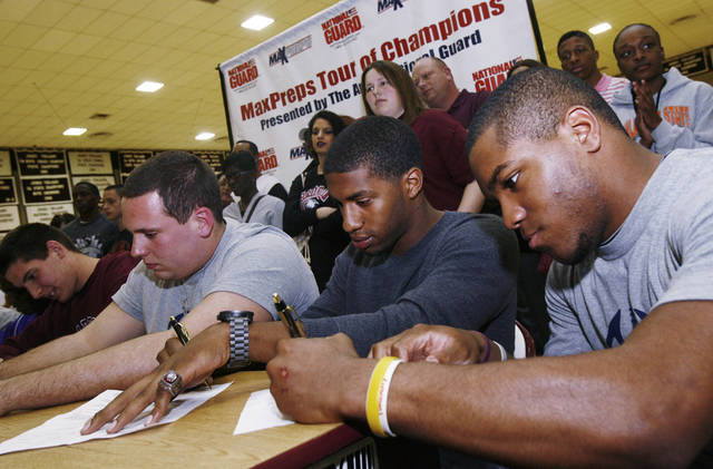 Members of the Jenks high school football team including Garrett Patterson (left), Brandon Waggoner, Trey'vonne Barre, and Braden Calip sign up for their new college teams, taken during signing Day in Jenks, Okla., on February 6,2013. JAMES GIBBARD/Tulsa World