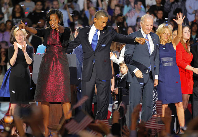 President Barack Obama , joined by his wife Michelle, Vice President Joe Biden and his spouse Jill acknowledge applause after Obama delivered his victory speech to supporters gathered in Chicago early Wednesday Nov. 7 2012. (AP Photo/Jerome Delay)