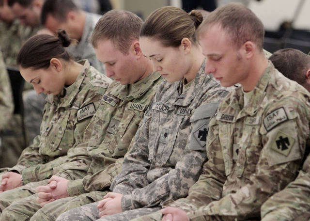 Returning members of the Oklahoma National Guard bow for a prayer as they are greeted by family and friends on their return from Afghanistan on Thursday, Jan. 12, 2012, in Norman, Okla.   Photo by Steve Sisney, The Oklahoman