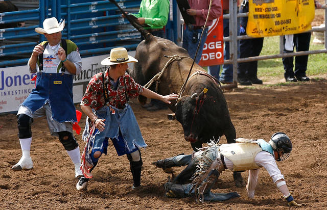 Josh Griggs of Fraser, Colo. crawls away as rodeo clowns get a bulls attention in the IYFR bull riding competition. The International Youth Finals Rodeo took place in Shawnee, Okla on Friday June 16, 2010. Photo by Mitchell Alcala, The Oklahoman