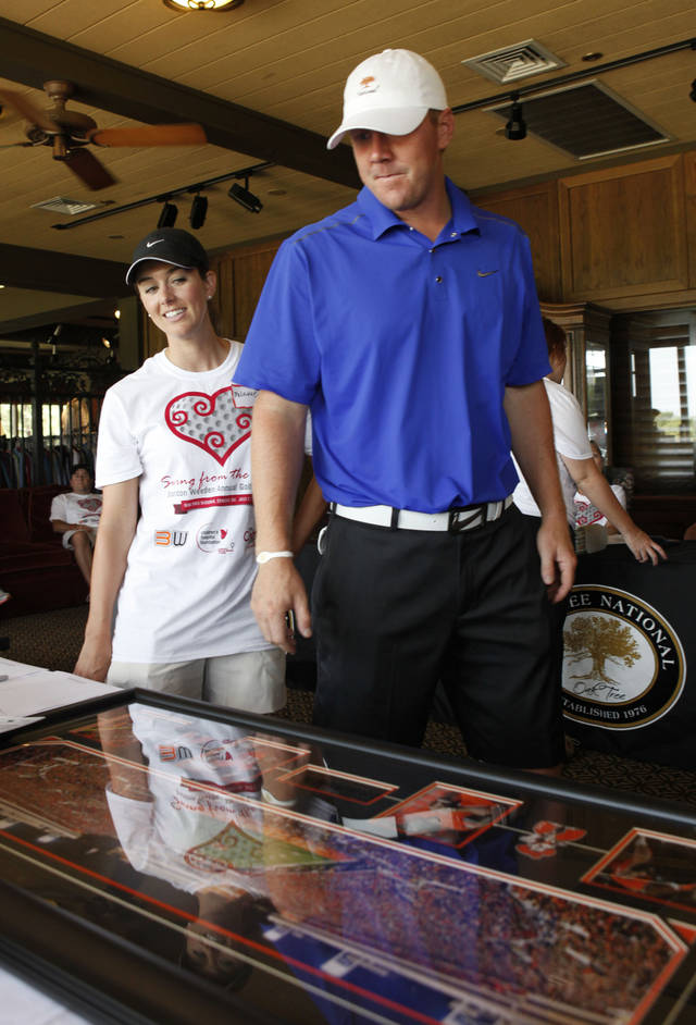 Brandon Weeden and wife Melanie look over some of his memorabilia after completing his charity golf tournament at Oak Tree National in Edmond, OK, Monday, July 23, 2012,  By Paul Hellstern, The Oklahoman