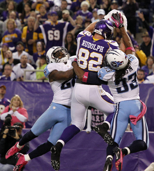 Minnesota Vikings tight end Kyle Rudolph (82) catches a 15-yard touchdown pass between Tennessee Titans' Jordan Babineaux, left, and Michael Griffin, right, during the second half of an NFL football game on Sunday, Oct. 7, 2012, in Minneapolis. (AP Photo/Genevieve Ross)