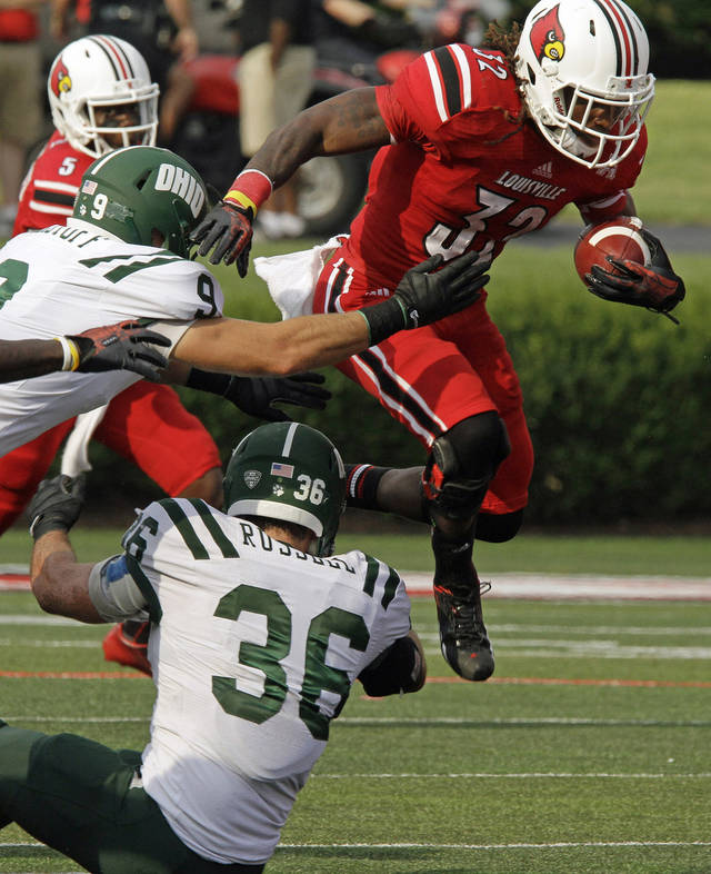 Louisville running back Senorise Perry (32) hurdles Ohio's Ben Russell (36) to get away from Ohio's Josh Kristoff (9) on a third-quarter run in an NCAA college football game in Louisville, Ky., Sunday, Sept. 1, 2013. (AP Photo/Garry Jones)