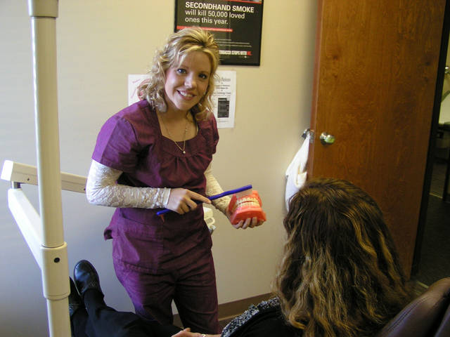 At the Good Shepherd Community Clinic in Ardmore, Dental Assistant Amanda Dethloff demonstrates brushingfor patient Debra Hart. Photo provided.   <strong></strong>