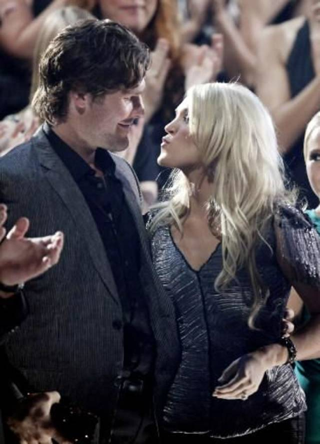 Checotah native Carrie Underwood gets a kiss from fiance Mike Fisher after she is named the winner of the top award, video of the year.