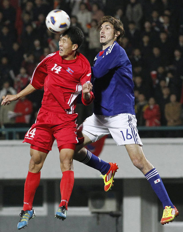 North Korea's Pak Nam Chol, left, and Japan's Mike Havenaar battle for the ball in the air in the second half of their 2014 World Cup qualifying soccer match at Kim Il Sung Stadium in Pyongyang, North Korea, Tuesday, Nov. 15, 2011. North Korea won the match 1-0. (AP Photo/Kyodo News) JAPAN OUT, MANDATORY CREDIT, NO LICENSING IN CHINA, FRANCE, HONG KONG, JAPAN AND SOUTH KOREA