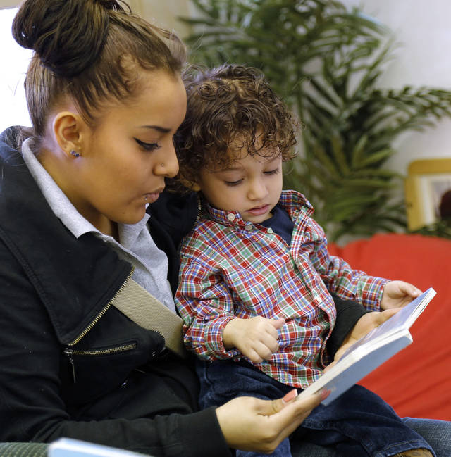 Karla Rodriguez reads Friday to her son, Izack Perez, 1. She hopes to benefit from the planned opening of a Variety Care health clinic at Emerson High School. Photo by Doug Hoke, The Oklahoman