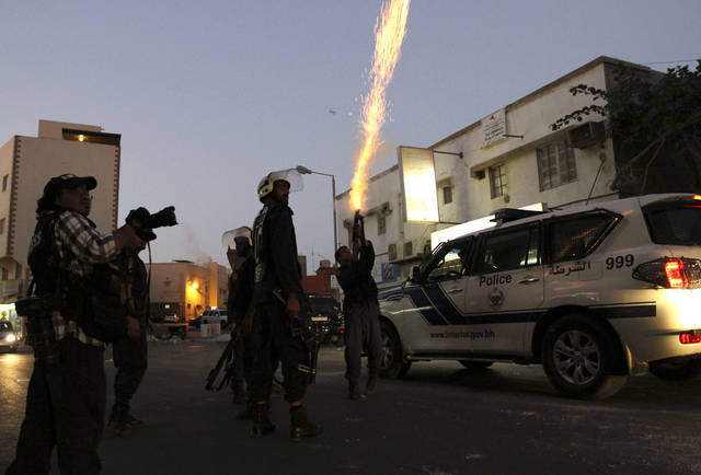 A riot policeman fires tear gas in Daih, Bahrain, on Saturday, Nov. 3, 2012, where Bahraini anti-government protesters tried to organize a march despite a ban on protests. A heavy police presence prevented protesters from gathering, and police dispersed and chased small groups through narrow streets as they emerged. (AP Photo/Hasan Jamali)