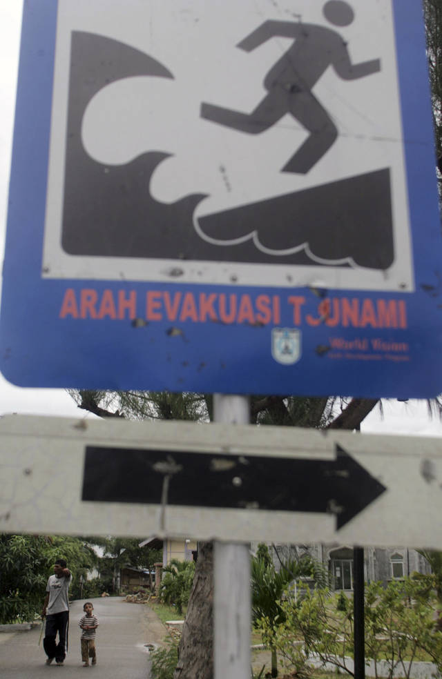 In this photo taken on Wednesday, April 18, 2012, residents walk near a sign showing a tsunami evacuation route in Banda Aceh, Aceh province, Indonesia. Residents living in tsunami-scarred Aceh province should prepare themselves for a possible repeat of the 2004 disaster, a leading seismologist said, noting historical data indicates tremendous stresses building up along the explosive fault could unleash again anytime within the next half century. (AP Photo/Heri Juanda)