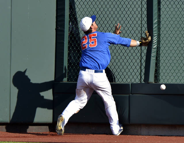 Florida right fielder Preston Tucker collides with the fence as he chases a ball hit for a triple by Kent State's David Lyon in the sixth inning of an NCAA College World Series elimination baseball game in Omaha, Neb., Monday, June 18, 2012. (AP Photo/Ted Kirk)